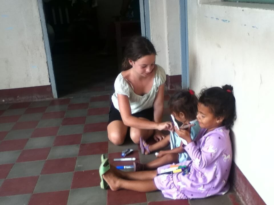Making the best of a bad situation. Amelia drawing with two girls at the police station. Photo by Nate